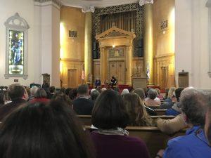 Man sieht das Innere einer Synagoge, Publikum von hinten und auf der Bühne Madeleine Albright und eine Journalistin, die ihr Fragen stellt.