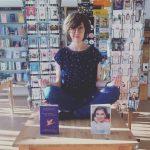 Lena Grimm sitzt auf einem Tisch in ihrer Buchhandlung in Yoga-Pose.