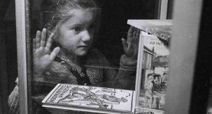 Eine kleines Mädchen bestaunt Bücher in einer Glasvitrine.