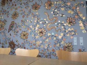 Zu sehen: Eine schöne, ornamentale Tapete hinter einem Tisch mit Stühlen.