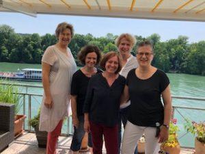 Fünf Frauen auf einer Terrasse vorm Rhein.