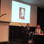 Auf einer Bühne sitzt die Autorin und das Jury-Mitglied, das ihr den Preis überreicht.