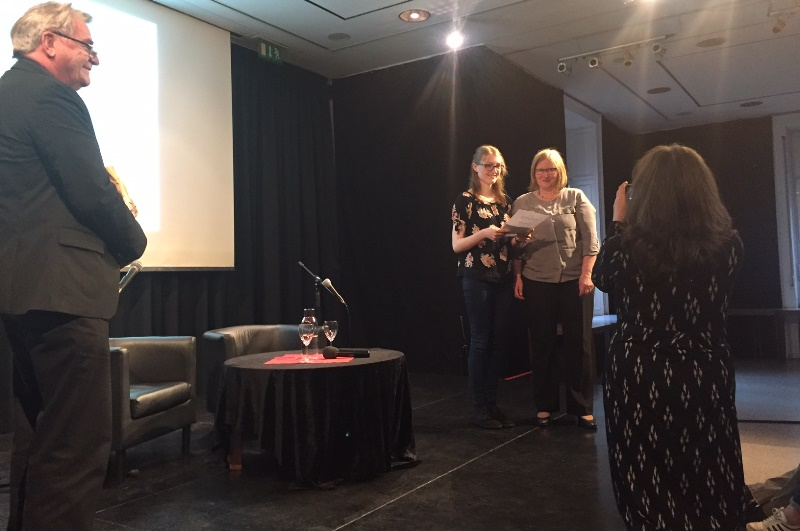 Zwei Frauen auf der Bühne, die Gewinnerin und eine Gratulantin, mit dem Rücken eine Fotografin und ein Jury-Mitglied