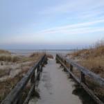 Ein sandiger Weg über eine Brücke zum Meer.