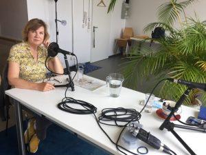 Silke Weniger sitzt an einem Tisch vor einem Podcast-Mikrofon.