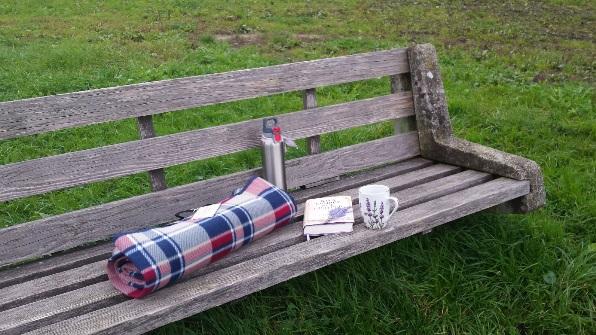 Zu sehen: Eine Bank mit Decke, Lektüre und Tee