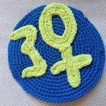 Gehäkeltes BF-Logo: Eine gelbe 30, statt 0 ein Venussymbol auf blauem gehäkeltem Grund