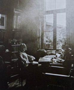 Die Schwarz-weiß-Fotografie zeigt Marie Luise Gothein in einem dunklen Zimmer mit großem Fenster.