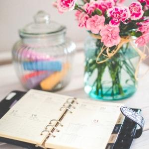Ein Kalender und eine Vase mit Blumen steht auf einem Tisch