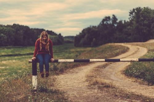 Ein Mädchen sitzt an einem Feldweg auf einer Schranke.