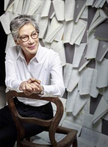 Eine sympathische Frau mit Kurzhaar-Frisur und Brille vor Büchern.